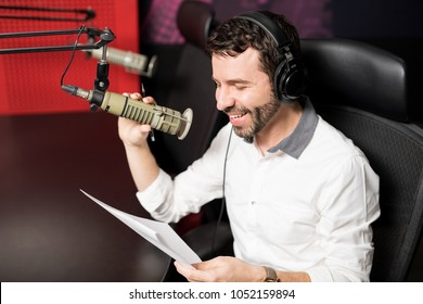 Smiling young male radio presenter with headphones reading a script and talking into a mic in a radio station