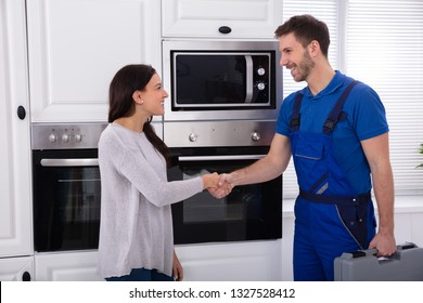 Smiling Young Male Serviceman Shaking Hands With Happy Woman