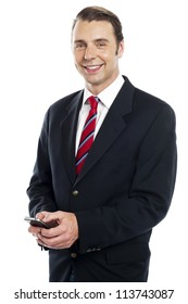 Smiling young male team leader sending text message to his colleagues