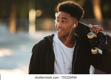 Smiling young male teenager guy with earphones holding skateboard on shoulders and looking away outdoors