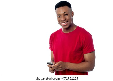 Smiling young male using his mobile phone.
