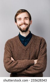 smiling young man with beard in brown sweater