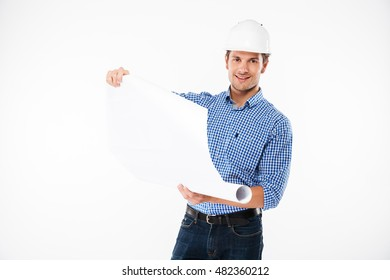 Smiling young man building engineer in helmet looking through blueprint