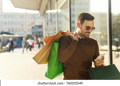 Smiling young man carrying shopping bags and looking at the notes