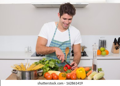 Smiling young man chopping vegetables in the kitchen at home