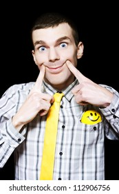 Smiling Young Man Comedian Putting On A Happy Face When Turning A Frown Upside Down, With Smile Ball In Pocket On Dark Black Copyspace Background