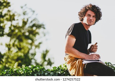 Smiling young man with curly hair, writing some notices on paper and preparing for exams, wearing black t-shirt sitting on the city street. Freelancer businessman makes plans for new projects.