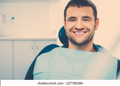 Smiling young man at dentist's surgery