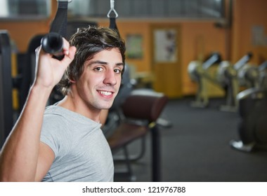 Smiling young man doing pulldowns in a fitness center