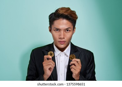 A smiling young man dressed in shirt and jacket showing two golden bitcoin and etherium isolated over gray background