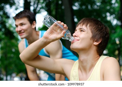 Smiling young man drinking after exercising at the park