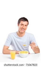 A smiling young man eating cornflakes at breakfast isolated on white background