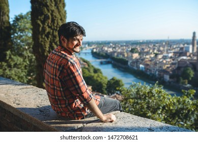 smiling young man enjoying view on river in Italy