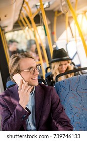 smiling young man in eyeglasses taling on smartphone in bus