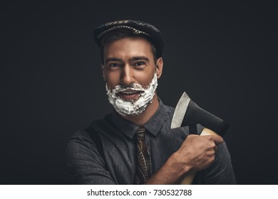 Smiling young man in flat cap and with shaving cream on his face, grooming his beard with an axe