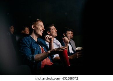 Smiling young man with friends in cinema hall watching movie. Group of people watching movie in theater.