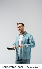 smiling young man with frying pan and spatula isolated on grey