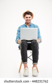 Smiling young man in hat sitting on chair and using laptop over white background