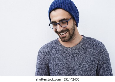 Smiling young man in hat and spectacles looking down