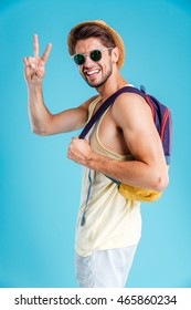 Smiling young man in hat and sunglasses with backpack showing peace sign over blue background