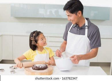 Smiling young man with his daughter preparing cookies in the kitchen at home