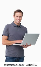 Smiling young man with his laptop against a white background