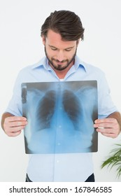 Smiling young man holding lung x-ray over white background