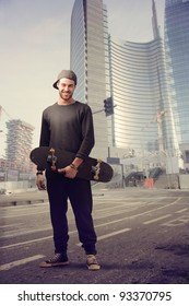 Smiling young man holding a skateboard on a city street