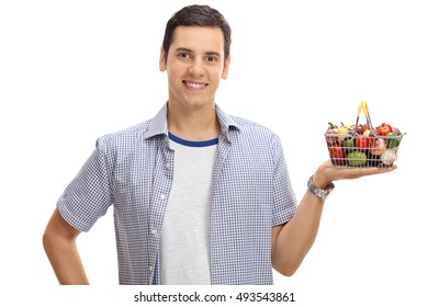Smiling young man holding a small shopping basket full of fruits and vegetables isolated on white background