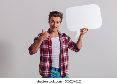 smiling young man holding speech bubble and makes the call me gesture on grey background
