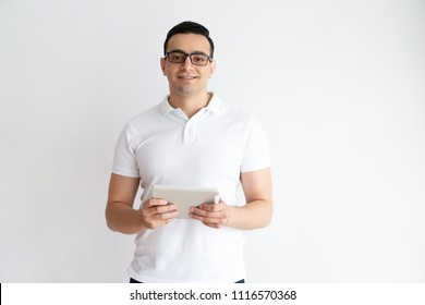 Smiling young man holding tablet computer. Handsome guy using digital gadget. Technology concept. Isolated front view on white background.