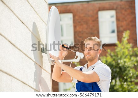 Smiling Young Man Installing TV Satellite Dish To Wall