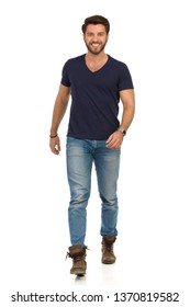 Smiling young man in jeans, boots and blue t-shirt is walking towards camera. Full length studio shot isolated on white.