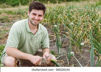 Smiling young man with knife, wearing on t-shirt and shorts, is sitting near the garlic garden bed, with green garden on background, waist up