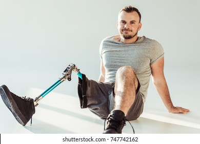 smiling young man with leg prosthesis looking at camera isolated on white
