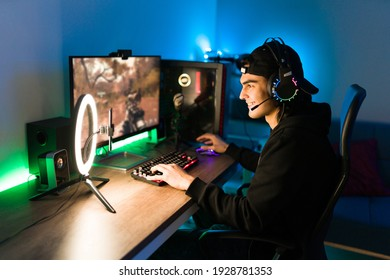 Smiling young man live streaming his online video game using a smartphone and a ring light. Happy gamer ready to start playing in a gaming computer