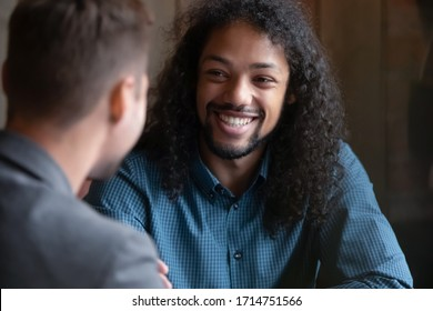 Smiling young man with long hair sit in cafe talking with male friend, happy overjoyed millennial guy meeting with colleague coworker, have fun chilling in coffeeshop together