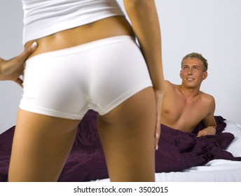Smiling young man, lying in bed in front of sexy woman. Gray background