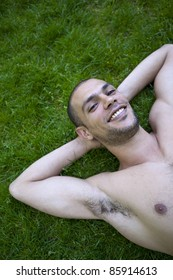 Smiling young man lying in the grass of a park
