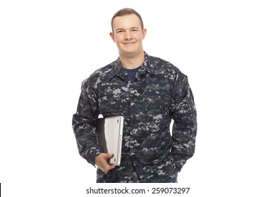 Smiling young man in navy uniform holding a laptop against white background