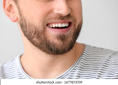 Smiling young man on light background, closeup