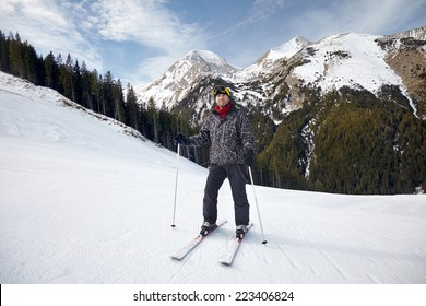 Smiling young man on skis in snow