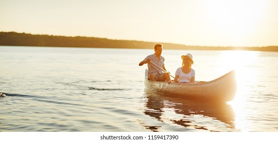 Smiling young man paddling a canoe on a lake with his girlfriend looking at the scenery on a late summer afternoon