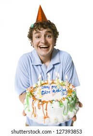 Smiling young man in party hat holding a birthday cake