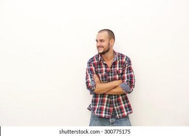 Smiling young man in plaid shirt standing with arms crossed against white background