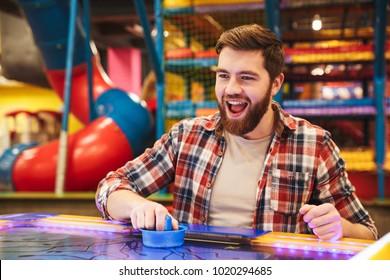 Smiling young man playing air hockey at Arcade centre