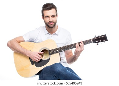 Smiling young man playing guitar isolated on white