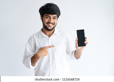 Smiling young man pointing at smartphone and looking at camera. Indian guy recommending product. Promotion concept. Isolated front view on white background.