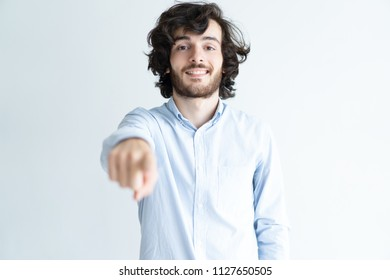 Smiling young man pointing at viewer and looking at camera. Guy choosing you. Promotion concept. Isolated front view on white background.