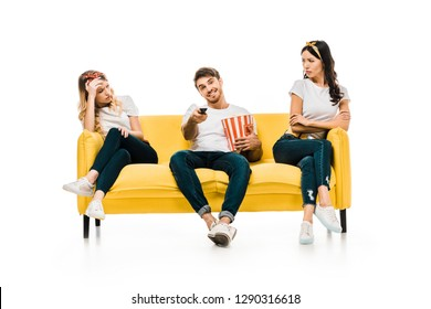 smiling young man with popcorn box and remote controller watching tv while bored and upset woman sitting on couch isolated on white